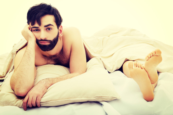 Upset man in bed thinks about vibrating cock ring